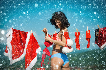 christmas new year snow concept Xmas red costume on rope with pin. Santa claus girl hanging clothes for drying. Christmas woman with buttocks outdoor. Laundry and dry cleaning. New year girl Foto de archivo