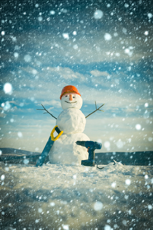 new year christmas snow concept Snowman builder in winter in helmet. New year snowman from snow with saw and screwdriver. Building and repair work. Happy holiday and celebration. Christmas or xmas Stock Photo