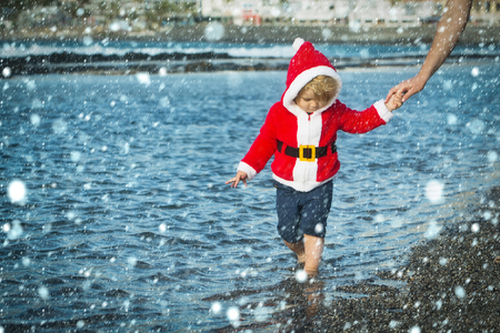 christmas new year snow concept Child holding female hand. Christmas and new year. Mothers day and family love. Winter holidays celebration concept. Boy in santa costume walking on sea beach. Banco de Imagens