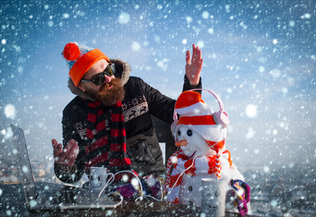 new year christmas snow concept xmas leisure and new technology. Santa claus man with snowman in hat. Snowman, winter holiday celebration. New year guy with laptop and headset, audio book. Christmas