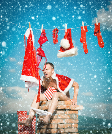 christmas new year snow concept New year guy with muscular body. Bad santa claus at clothes for drying shit on chimney. Xmas red costume on rope with pin. Laundry and dry cleaning. Christmas man with
