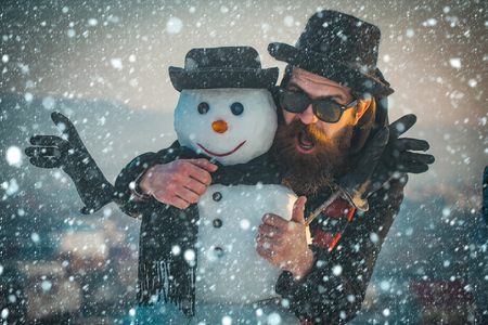 new year christmas snow concept Christmas man with beard on happy face. xmas leisure and winter season. Santa claus man with snowman in black hat. Snowman, winter holiday celebration. New year guy Stock Photo