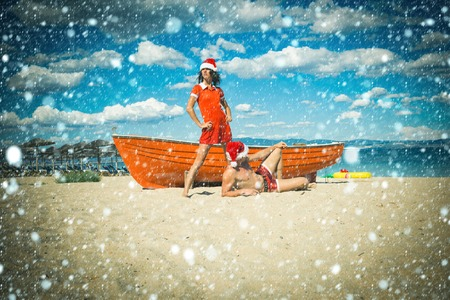 new year christmas snow concept New year girl and guy as santa. Xmas party celebration. Winter holiday and vacation. Christmas couple in red at beach boat. Couple in love of happy man and woman Stock Photo
