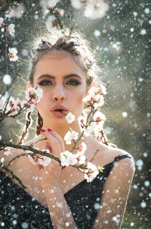new year christmas snow concept girl and flowers. pretty woman eating white cherry or apricot spring flower blooming, has fashionable makeup on face and stylish hair sunny outdoor natural background Stock Photo