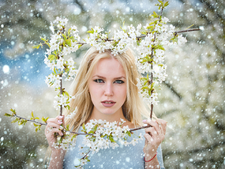 christmas new year snow concept spring, girl near a flowering tree with frame of blossom