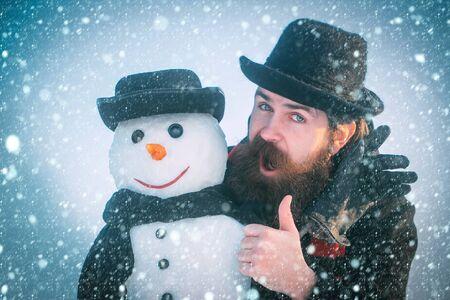 Nieuwjaar Kerstmis sneeuw concept Man of hipster met baard geven duimen omhoog hand. Sneeuwpop met smileygezicht in handschoenen. Heren in zwarte hoeden en sjaals op blauwe hemel. Kerstmis en Nieuwjaar concept