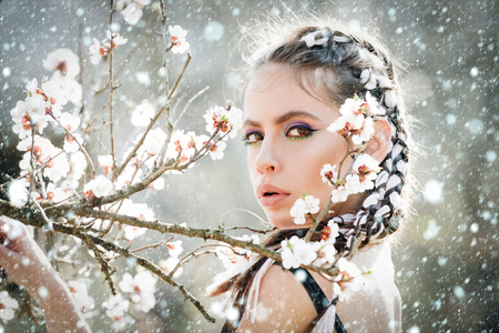 new year christmas snow concept woman in beautiful spring flower blossom in garden with fashion makeup on summer natural background, youth and health