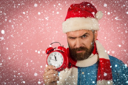 christmas new year snow concept Christmas new year, xmas holidays celebration. Man with frown face hold alarm clock. Time to celebrate concept. Hipster in santa hat, scarf on pink background. Stock Photo