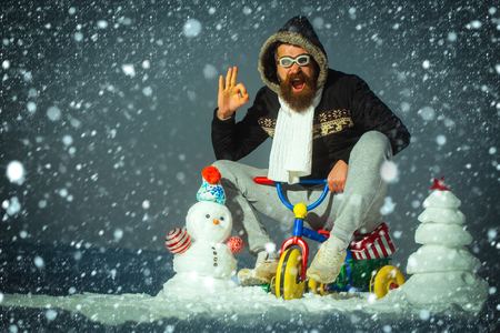 christmas new year snow concept Happy man riding tricycle on grey sky. Hipster in pilot glasses and hood showing ok gesture. Christmas and new year fun. Snowman and snow xmas tree on winter landscape