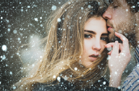 christmas new year snow concept Sexy man and girl with fashion makeup and long hair touching each other with love and tenderness. Young couple of heterosexual lovers outdoors Stock Photo