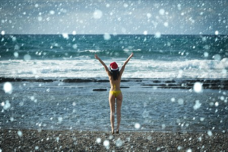 christmas new year snow concept Woman in santa claus hat rising hands to blue sky. Freedom concept. Girl in sexy swimsuit standing on sea beach. Christmas and new year celebration Stock Photo
