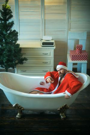 Winter holiday and xmas party. Christmas man with beard, waiting. Expectation, love and betrayal. Hipster santa at Christmas tree drink wine, loneliness. Home alone, bad santa in bath.