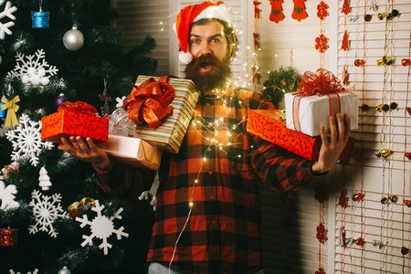santa claus man at decoration and garland. New year guy with illuminated wire , present box and toy. Winter holiday and xmas. Party and celebration. Christmas man with beard on happy face and garland.