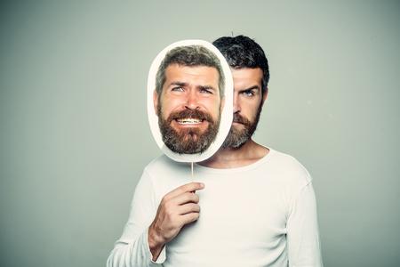 Hipster met serieus en eng gezicht houdt portret naamplaatje. Man met lange baard en snor. Man of bebaarde man op grijze achtergrond. Kapper mode en schoonheid. Gevoel en emoties. Stockfoto