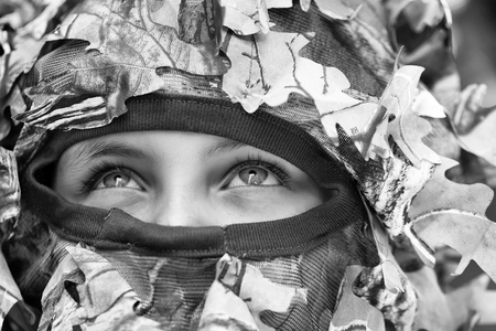 Little girl with blue serious strict eyes in military helmet with net and mask with closed face war camouflage Stok Fotoğraf - 92512998