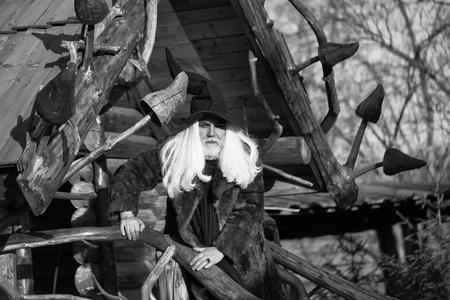 黒いハロウィーンの帽子で長い銀髪とひげを持つ古いドルイドの男は、ログハウスの背景に晴れた日に屋外に立っています