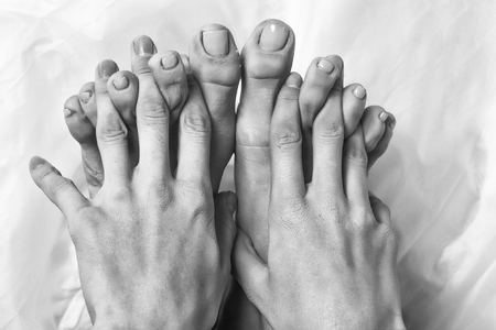 Female fingers between toes on white background. Beautiful hands and feet with nude nail manicure and pedicure Stock fotó