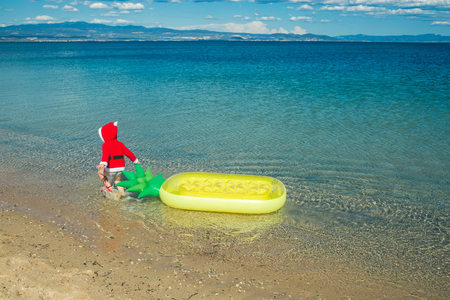 christmas happy child in red santa claus costume at sea or ocean water beach with pineapple mattress, summer and winter vacation, new year holiday and party celebration, childhood