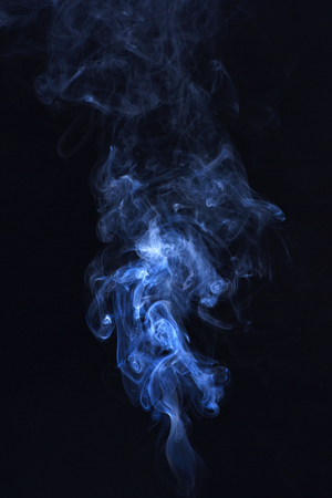 Blue ink in freeze motion, powder splatted explosion. Smoking cloud backdrop. Blue smoke on black background. Abstract background with smoke. Spirit and ghost, miracle.
