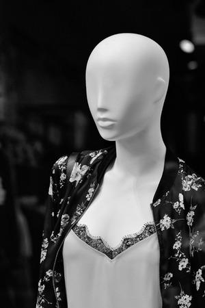 Manier vrouwelijke ledenpop kaal in vrije tijdslijtagekleren in winkel op donkere achtergrond Stockfoto