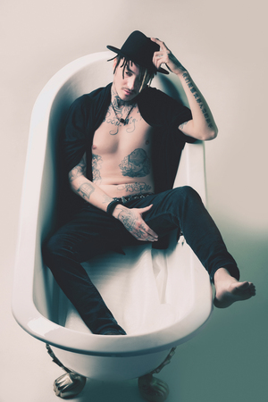 Guy showing tattooed torso and hands. Man in black hat and clothes lying in bath tab. Art on skin. Tattoo studio concept. Fashion and accessories.