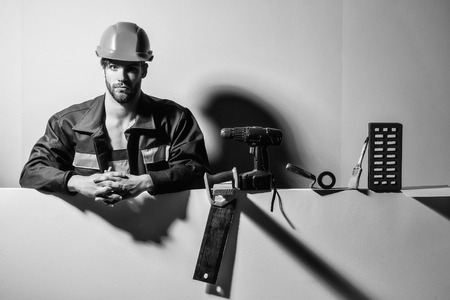 Handsome man bearded male builder repairman craftsman foreman or construction worker in orange hard hat and boilersuit with technical tools on colorful background