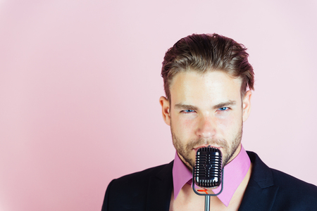Music, look and retro style, freak. man sing in microphone. dj young man on pink background, radio. singer with stylish retro hair, show business, copy space