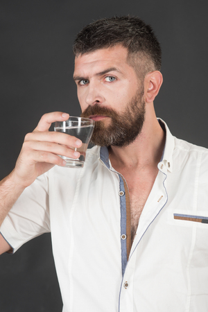 Man with long beard hold water glass on grey background. Hipster drink clean healthy water, refreshing. Hangover and thirst. Health and dieting. Life source and healthcare.