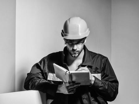 オレンジ色のハードハットとボイラースーツでハンサムな男ビルダー修理工職人の職人や建設労働者は、灰色の背景に会計帳簿を保持します