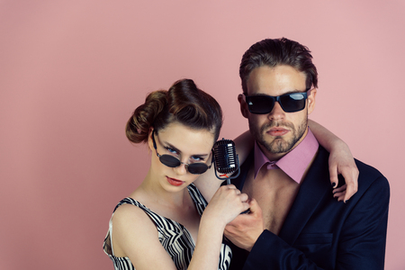 Couple in love in glasses sing in microphone. Singer man and woman with retro hair and makeup. Pinup girl and man on pink background, radio. Beauty and vintage fashion, music band. Music and love.