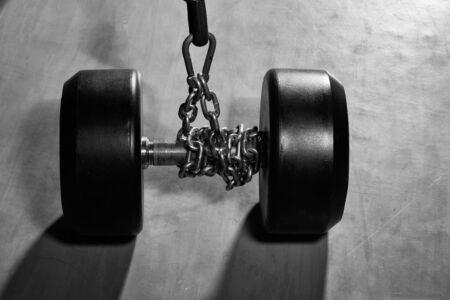 Schwerer Gummidummkopf des metallischen oder Stahls, Gewichthebenausrüstung auf Eisenkette für Gewichtstraining, Sport, Training in der Eignungsturnhalle auf grauem Bodenhintergrund Standard-Bild - 92048026