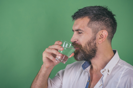 Life source and healthcare. Hangover and thirst. Health and dieting. Man with long beard hold water glass on green background. Hipster drink clean healthy water, refreshing.