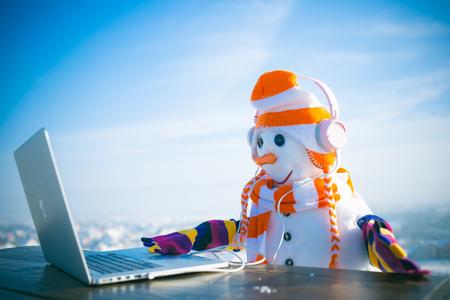 Schneemann im Winter mit Laptop, Kopfhörer und Teetasse. Weihnachts- oder Weihnachtsdekoration, Hörbuch. Frohe Festtage, neue Technologie. Schneemann des neuen Jahres im Hut. Weihnachten und heißer Wein ..