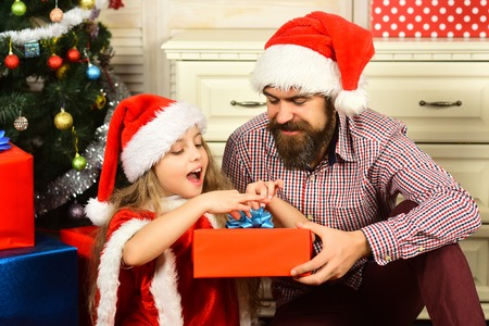 Happy family celebrate new year and Christmas. Father and child with present box. Father and daughter in santa hat at Christmas tree. Xmas party celebration. Winter holiday and New year.