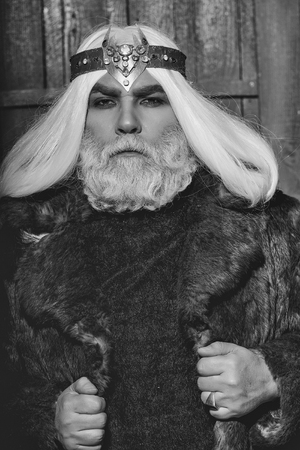 old druid bearded man with long beard on serious face and hair in fur coat and crown with gem stones jewellery