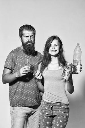 美しい長い髪の女の子とハンサムなひげの男の笑顔のカップルは、灰色の壁に水のボトルリンゴとガラスを保持します 写真素材