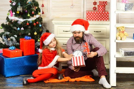 Happy family celebrate new year and Christmas. Father and child with present box. Xmas party celebration. Father and daughter in santa hat at Christmas tree. Winter holiday and New year.