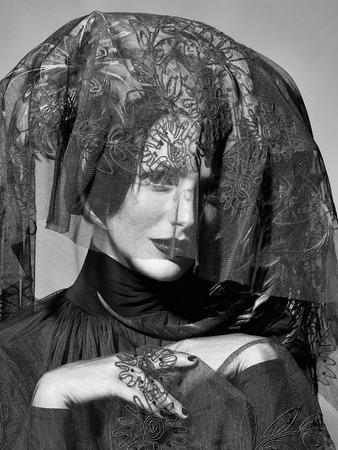 ハロウィーンやカーニバルの休日の衣装や灰色の背景にベールとして美しい羽の帽子茶色の色できれいな顔に赤い唇を持つ若いセクシーな女性や女