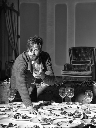 Handsome young man with beard and blond hair eats vegetables with wine in glass from dirty plates with leftovers or residues of food after banquet dinner on table in restaurant Reklamní fotografie