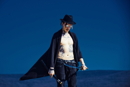 Warrior in black hat and open clothes showing tattooed torso. Man with katana sword standing on dark blue sky. Concentration and zen. Martial arts concept. Samurai and japan weapon.