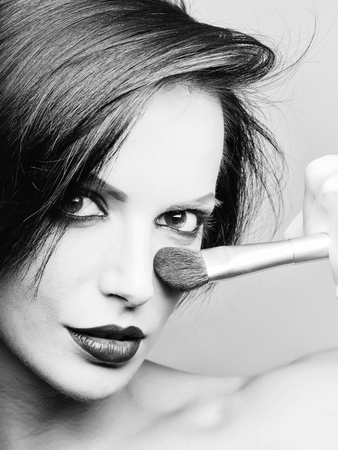 Girl with short dark hair red lips and make up with face brush applies blush on her nose in front of grey background