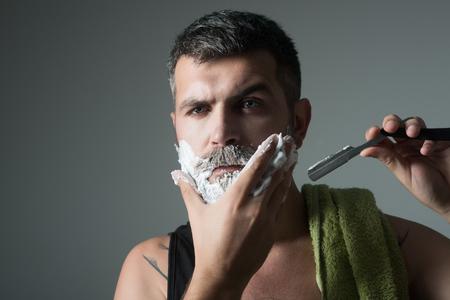 ファッションと美しさ、革新。あごひげ男の散髪、考古学。理髪店の深刻なヒップスター、新しい技術。床屋と美容師男はかみそりと剃毛ブラシで 写真素材