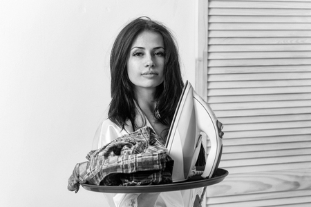 Pretty girl or beautiful woman, housewife, with long brunette hair in sexy dressing gown with electric iron and clothes for ironing on tray on white wall. Housework and housekeeping