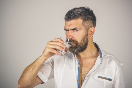 Health and dieting. Hangover and thirst. Life source and healthcare. Man with long beard hold water glass on grey background. Hipster drink clean healthy water, refreshing. Imagens - 92574702