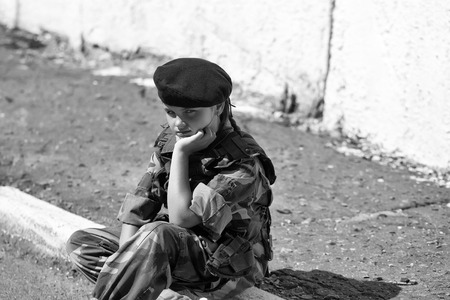 Young girl child with pretty sad thoughtful face in army camouflage ammunition and black beret sitting on stone ground outdoor Stock Photo