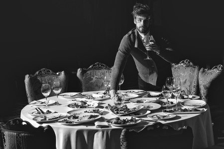 Handsome young man with beard and blond hair drinks wine from glass over table with leftovers or residues food on dirty plates after banquet dinner in restaurant on dark background