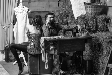 Bearded man tailor or dressmaker and pretty girl customer or sexy model with curly brunette hair and undressed back sit near vintage sewing machine in rustic workshop Imagens