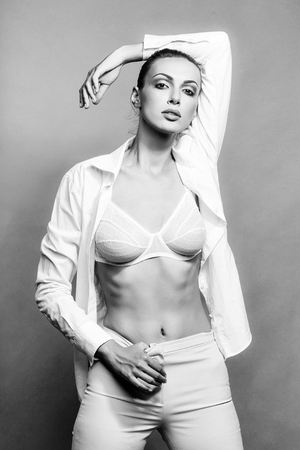 young stylish woman or girl with glamour makeup on pretty face in fashionable white shirt and bra on slim sexy body posing in studio on grey backgroud