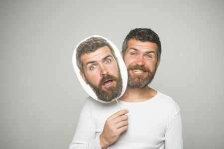 Barber fashion and beauty. Feeling and emotions. Hipster with surprised and happy face hold portrait nameplate. Guy or bearded man on grey background. Man with long beard and mustache. Banco de Imagens