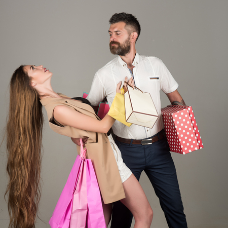 shopping and sale, happy couple in love of woman with long hair and bearded man hold shopping bag or present back on grey background, holiday, black friday